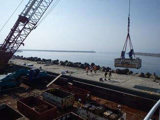 山木工業保有のクレーン船で松下埠頭に到着した資材を1時間半をかけて打ちあげ場所の西防波堤に運搬しました